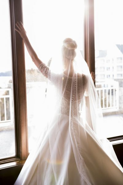 Beautiful bride gazes out the window at the Osthoff Resort- Image by Wild Elegance