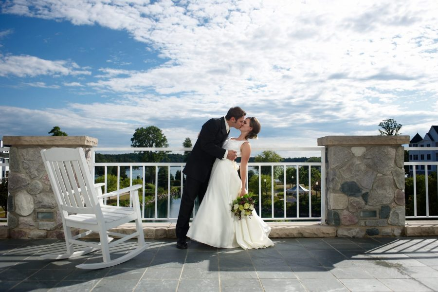 Groom kisses bride on balcony at the Osthoff Resort