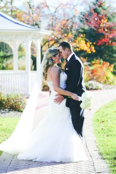 Bride and groom embrace by the gazebo at the Osthoff Resort