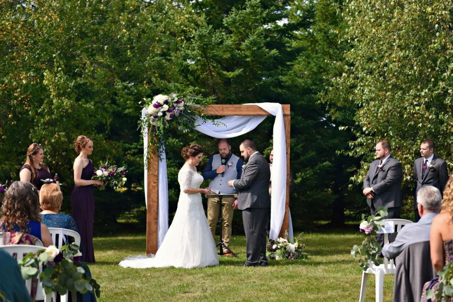 Couple exchange vows under wooden arch adorned with lush florals