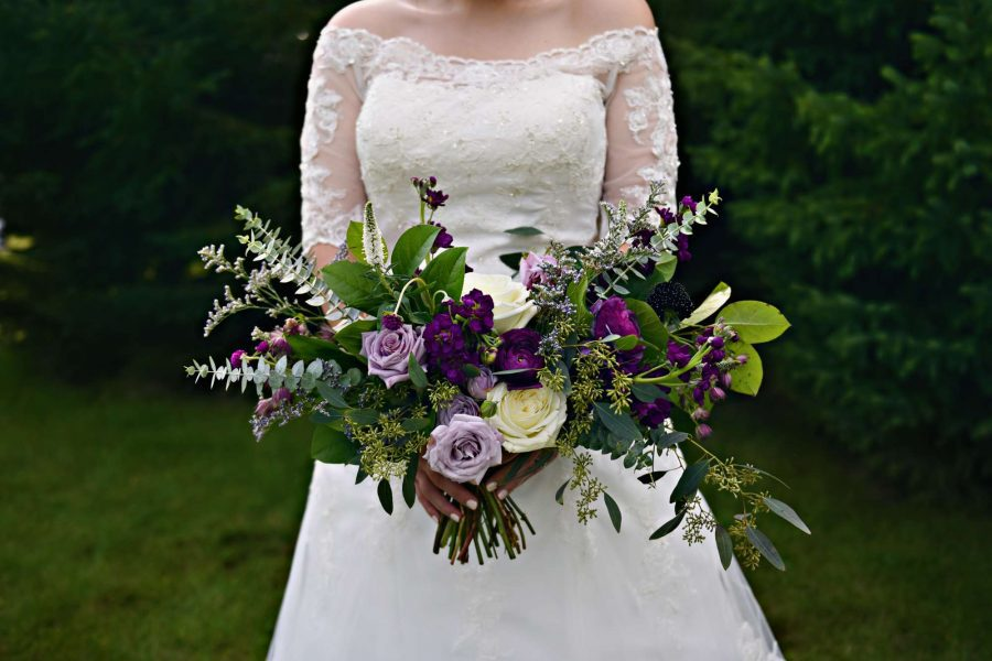 Beautiful brides bouquet in shades of violet, with lush greenery and white floral accents. Created by 88 Events