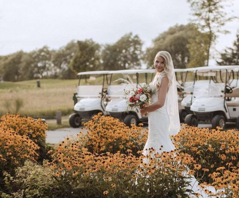 bride standing in flowers near gold carts at Par 5 Resort in Mishicot, WI