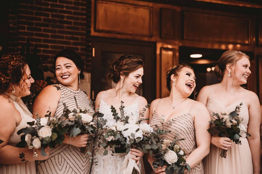 Bride and bridesmaid laughing and holding their bouquets by 88 Events
