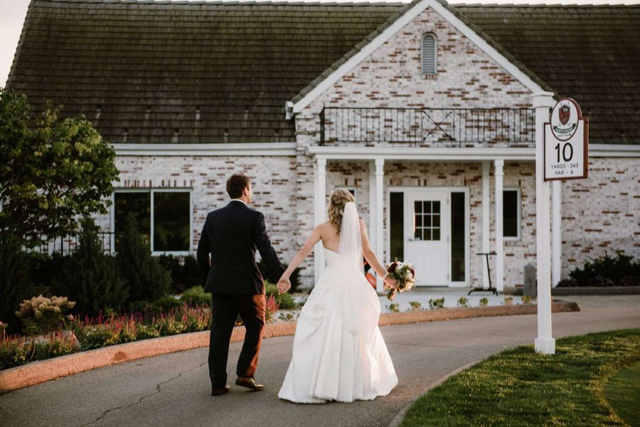 Bride and groom walking towards the North Shore Golf Club