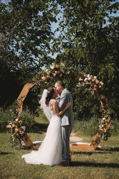 Bride and Groom kiss under curved floral drenched arch- 88 Events