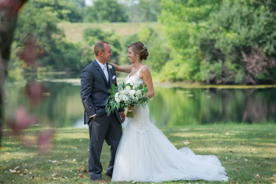 Bride and Groom pose by pond. Classic white bridal bouquet by 88 Events.