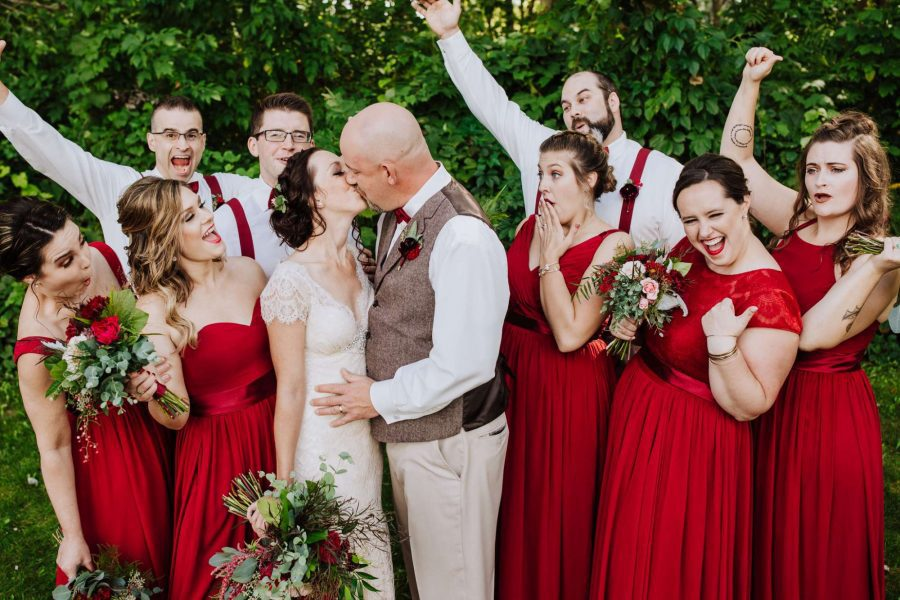 Bride and groom kiss while wedding party looks on
