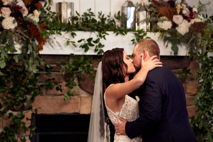 Bride and groom kiss in front of floral draped fireplace mantel
