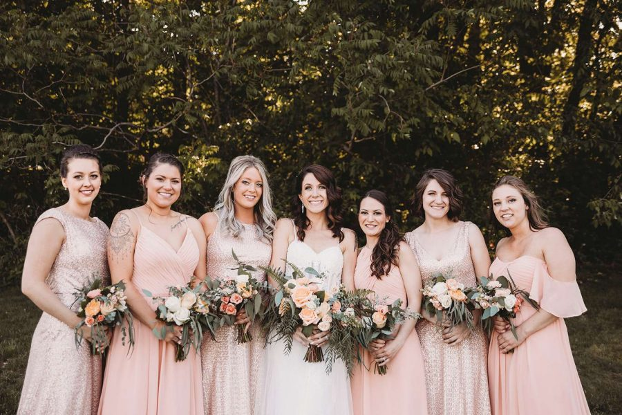Wedding party poses with their bouquets in soft peach hues by 88 Events
