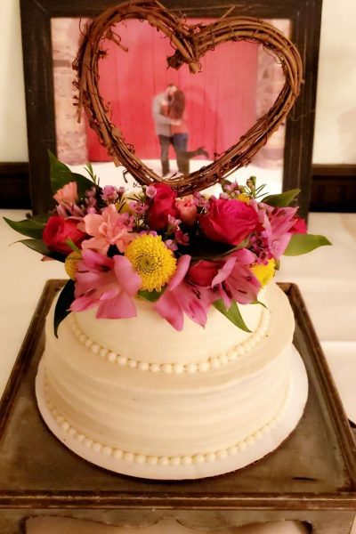 White wedding cake adorned with fresh flowers and a heart by Cupcake Couture