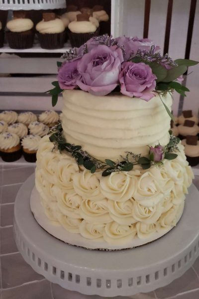 Creamy white cake with lavender rose accents by Cupcake Couture