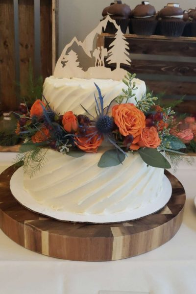 Classic white wedding cake with fresh floral accents by Cupcake Couture