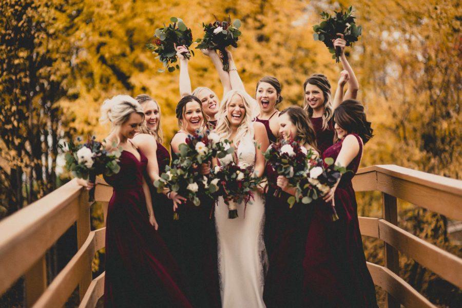 Bride and bridesmaids on walk bridge in fall at the EAA in Oshkosh