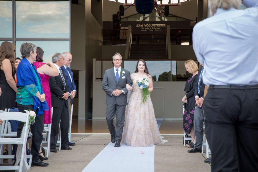 Bride walks down aisle with hr father at EAA Wedding ceremony in Oshkosh, WI