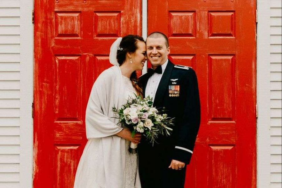 Bride & groom pose near red doors of Fergus Chapel at the EAA Aviation Center in Oshkosh, WI