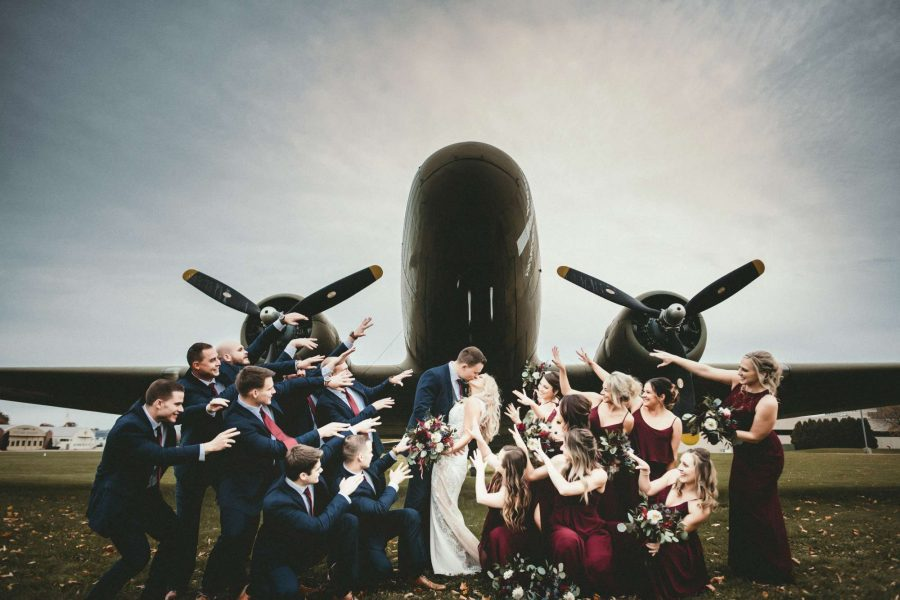 Wedding party poses by airplane at the EAA Aviation Center in Oshkosh