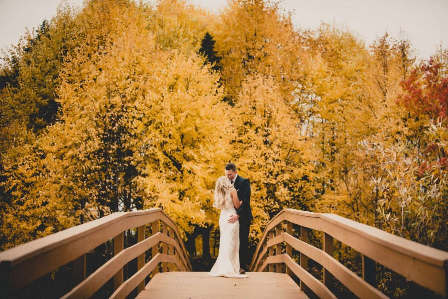 Bride and groom on walk bridge in fall at the EAA Center grounds in Oshkosh