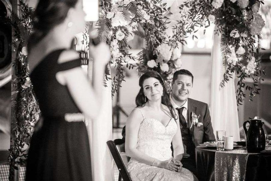 Bride & groom listen on as bridesmaid gives speech at EAA Aviation Center wedding reception