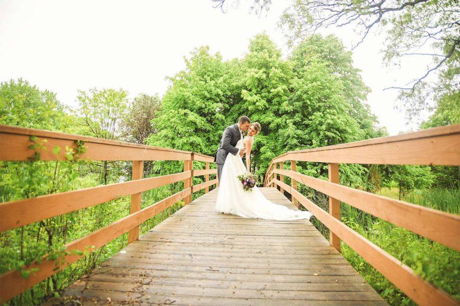 Bride & groom on walk bridge at their EAA Aviation Center wedding