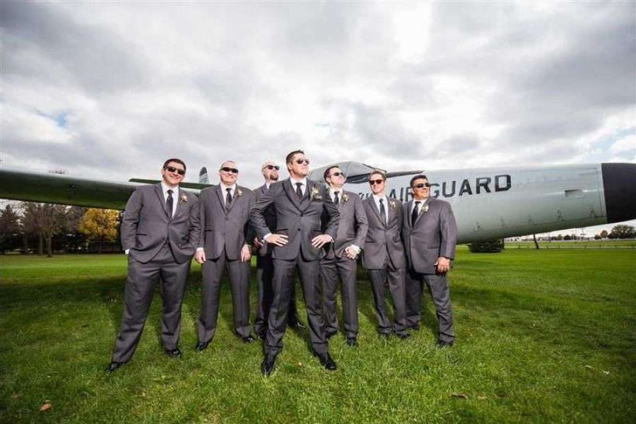 Groom and groomsmen pose by airplane at the EAA in Oshkosh, WI