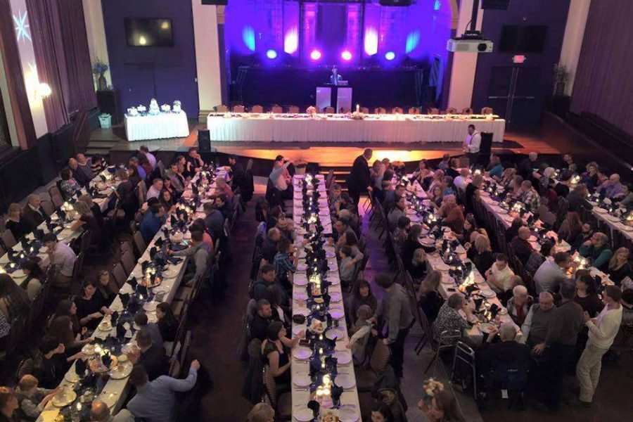 Wedding reception with long tables and dramatic up lighting at the Outer Edge in Appleton, WI