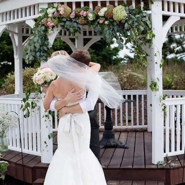 Bride and groom embrace by gazebo at Par $ Resort in Waupaca, WI
