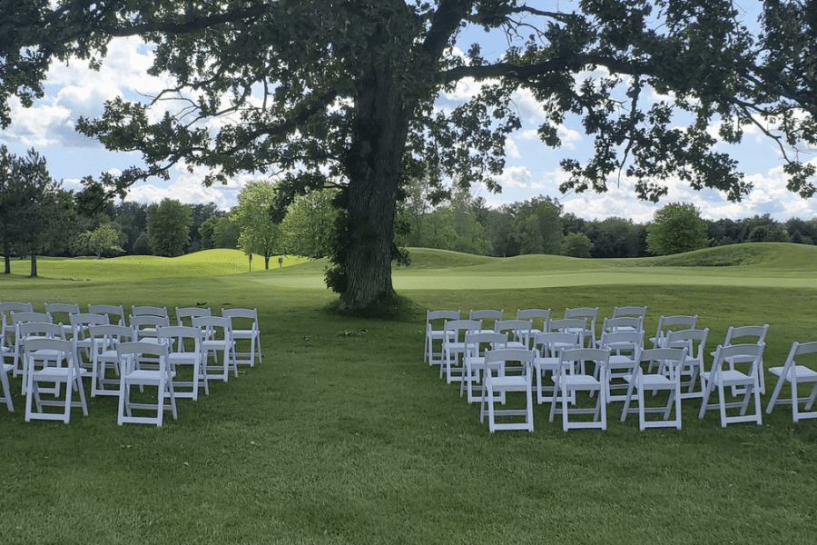 Golf course wedding ceremony set up with white chairs at Par 4 Resort