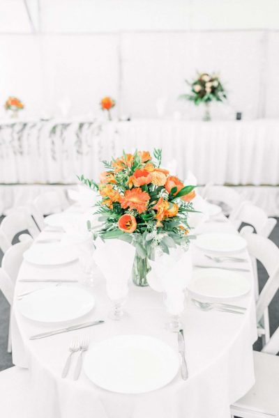 Tented wedding reception in white with bright florals at Par4 Resort in Waupaca, WI