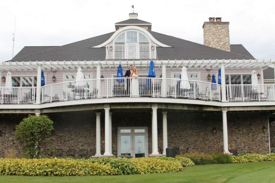 Bride and groom stand on balcony at the Manor at Pinehurst Farms