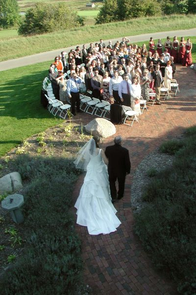 Bride being walked down aisle by her father at outdoor ceremony at the Manor at Pinehurst Farms